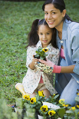 Hispanic mother and daughter planting flowers in backyard
