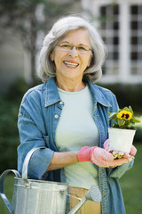 Senior Hispanic woman holding gardening tools outdoors