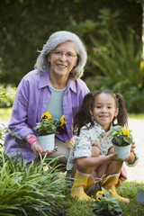 Hispanic grandmother and granddaughter gardening in backyard