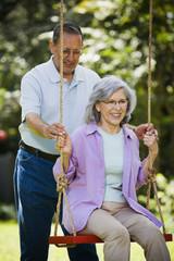 Senior Hispanic man pushing wife on swing