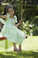 Hispanic girl in party dress on swing
