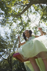 Low angle view of Hispanic girl in party dress on swing
