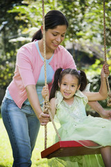 Hispanic mother pushing daughter on swing
