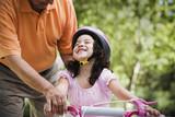 Hispanic man helping granddaughter ride bicycle