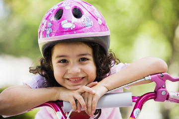 Hispanic girl leaning on bicycle outdoors