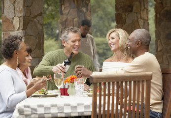 Friends drinking wine at dinner party