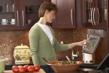 Hispanic woman touching flat screen computer in kitchen