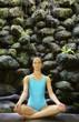 Pacific Islander woman in bathing suit meditating