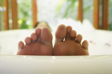 Close up of woman's feet in bubble bath