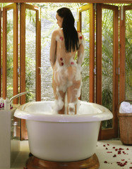 Nude Pacific Islander woman standing in bubble bath