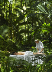 Pacific Islander woman receiving massage in jungle