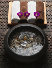 Bowl with water and pebbles next to rolled towels