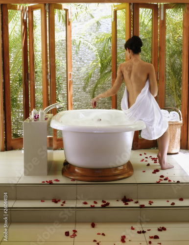 Pacific Islander woman sitting on edge of bathtub