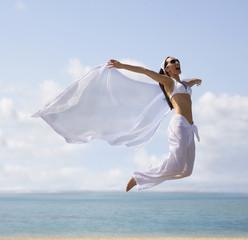 Pacific Islander woman jumping at beach