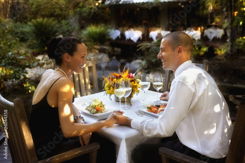 Couple holding hands at restaurant table