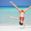 Woman doing hand stand at beach