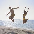 Couple jumping at beach