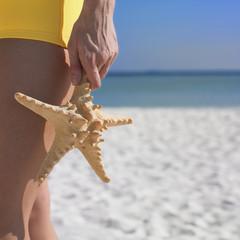 Woman holding starfish at beach
