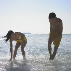 Couple playing in water at beach