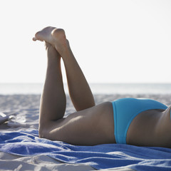 Woman laying on beach towel