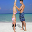 Man helping girlfriend do handstand at beach