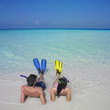Couple wearing snorkeling gear at beach