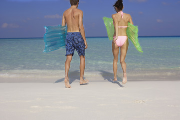 Couple walking into ocean with pool rafts