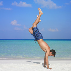 Man doing hand stand at beach