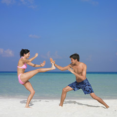Couple Kung Fu fighting at beach