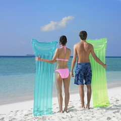 Couple holding pool rafts at beach