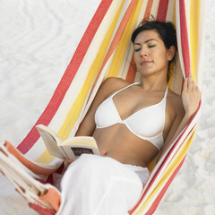Woman reading in hammock at beach