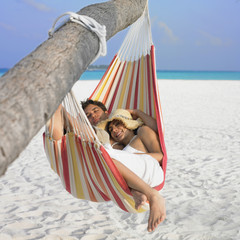 Couple laying in hammock at beach
