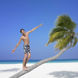 Man standing on palm tree at beach