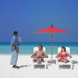 Maldivian man serving drinks to couple at beach