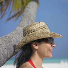 Woman next to palm tree at beach
