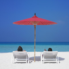 Couple in beach chairs under umbrella