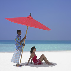 Maldivian man holding beach umbrella over woman