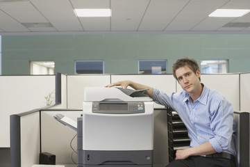 Businessman sitting next to copy machine