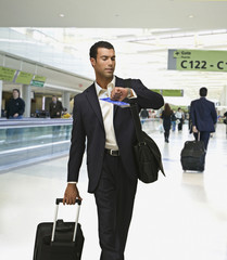 Hispanic businessman checking time in airport