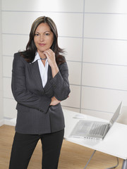 Hispanic businesswoman posing by office desk