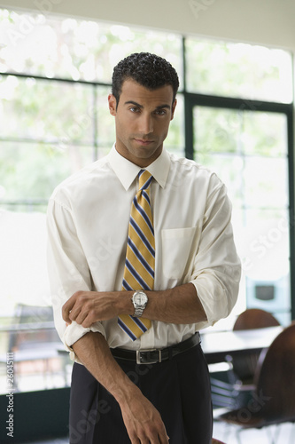 Hispanic businessman rolling up sleeves