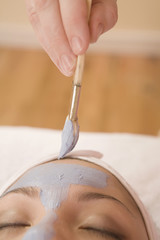 Close up of mud mask being applied to woman's face