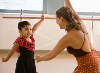 Hispanic teacher and girl in dance class