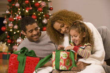 Mixed race family opening Christmas gifts