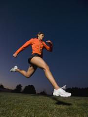 Mixed race woman running on grass