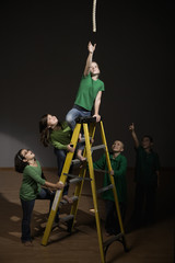 Children supporting girl on ladder reaching for rope