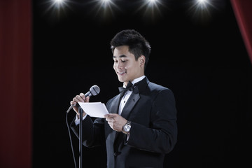 Asian man in tuxedo reading notecards at microphone