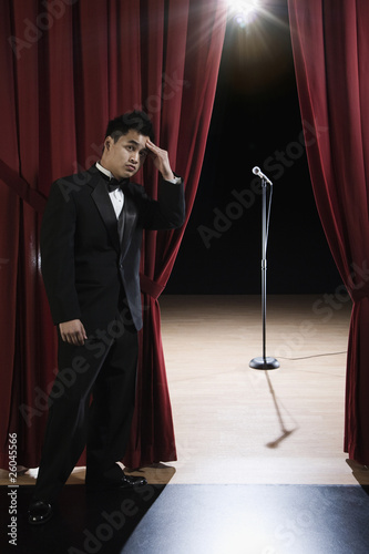 Asian man in tuxedo looking nervous backstage