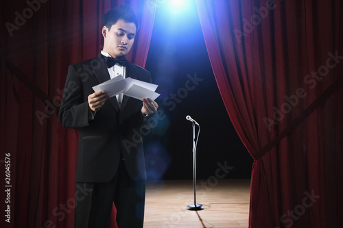 Asian man in tuxedo reviewing notecards backstage