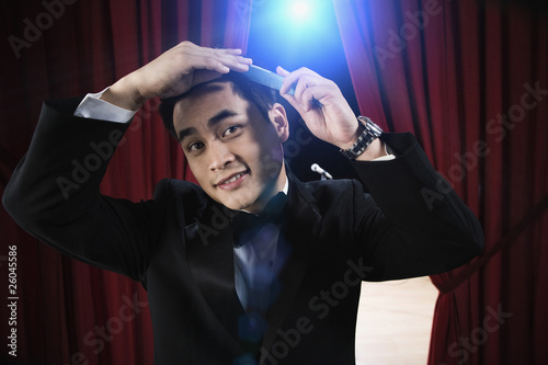 Asian man in tuxedo combing hair backstage